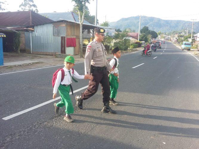 Bantu Anak Sekolah Menyeberang Jalan, SatSabhara Polres Lampung Barat Berikan Layanan Keamanan